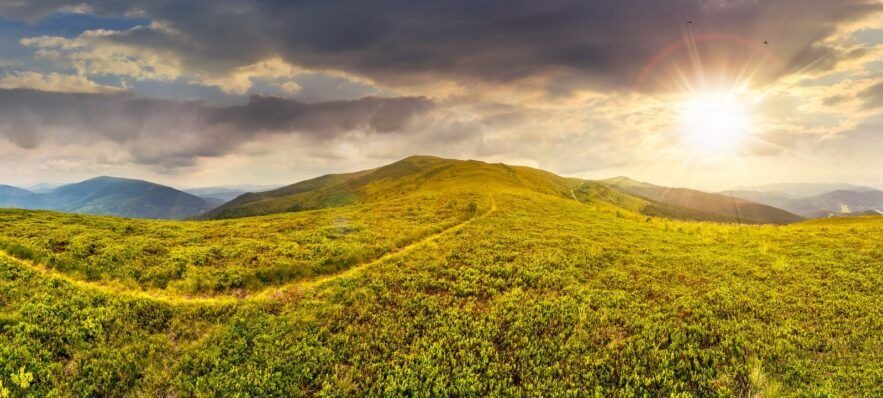 path among the grass on mountain top at sunset